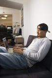 De zitting van de mens op bank die laptop met behulp van. Royalty-vrije Stock Afbeelding