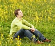De zitting van de mens op een bloemgebied stock afbeeldingen