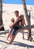De zitting van de mens op een logboek met zijn zoon en dochter royalty-vrije stock afbeelding
