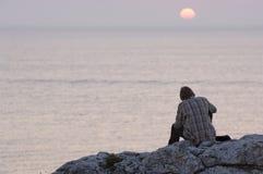 De zitting van de mens op een rots Stock Foto