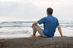 De zitting van de mens op een rots bij het overzees Stock Fotografie