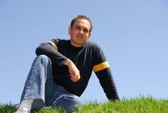 De zitting van de mens op gras Royalty-vrije Stock Afbeeldingen