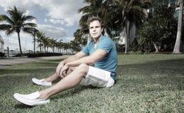 De zitting van de mens op het gras Royalty-vrije Stock Foto's