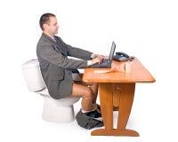 De zitting van de mens op het toilet stock afbeelding