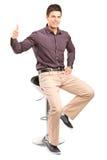 De zitting van de mens op hoge stoel en het opgeven van duim Stock Afbeelding