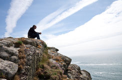 De zitting van de mens op klippenbovenkant royalty-vrije stock foto