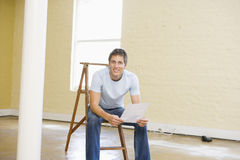 De zitting van de mens op ladder in een lege ruimte met document royalty-vrije stock foto