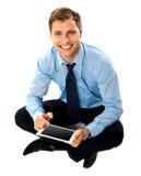 De zitting van de mens op vloer die het apparaat van het aanrakingsscherm met behulp van stock afbeeldingen