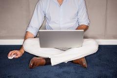 De zitting van de mens op vloer met laptop in bureau stock fotografie