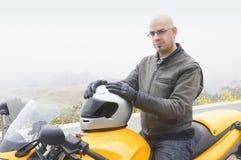 De zitting van de mens op zijn motorfiets Royalty-vrije Stock Foto