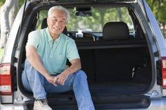 De zitting van de mens in rug van bestelwagen het glimlachen Stock Afbeeldingen