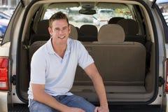 De zitting van de mens in rug van bestelwagen het glimlachen royalty-vrije stock foto's