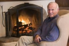 De zitting van de mens in woonkamer door open haard te glimlachen stock foto