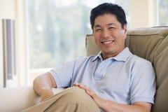 De zitting van de mens in woonkamer het glimlachen Stock Foto