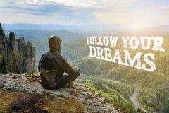 De zitting van de mensenwandelaar bovenop berg en overweegt mooie mening aan de vallei Volg uw dromen het van letters voorzien stock foto's