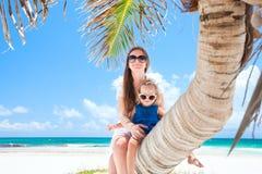 De zitting van de moeder en van de dochter op palm Royalty-vrije Stock Afbeeldingen