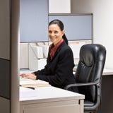 De zitting van de onderneemster bij bureau het glimlachen stock foto