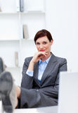 De zitting van de onderneemster in bureau met voeten op bureau Stock Afbeeldingen