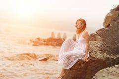 De zitting van de roodharigevrouw op de kust op strand royalty-vrije stock fotografie