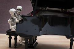 De zitting van de skeletpiano Stock Afbeeldingen