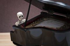 De zitting van de skeletpiano Stock Foto