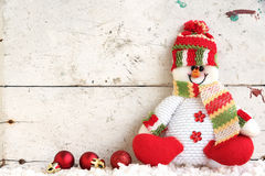 De zitting van de sneeuwmanpop op de sneeuw met Kerstmisbal Royalty-vrije Stock Afbeeldingen