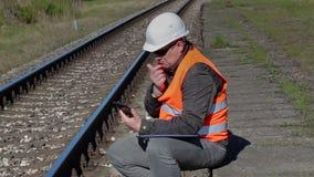De zitting van de spoorwegarbeider en het denken dichtbij spoorweg stock footage