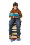 De zitting van de student op een stapel van boeken Royalty-vrije Stock Fotografie