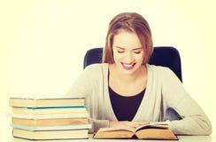 De zitting van de studentenvrouw door het bureau met boeken Stock Foto's