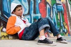 De zitting van de tiener dichtbij een graffitimuur Stock Afbeelding