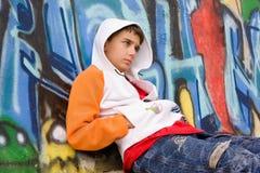 De zitting van de tiener dichtbij een graffitimuur Stock Foto's