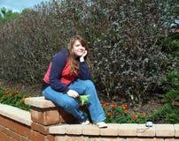 De zitting van de tiener op de tuindeurpost Royalty-vrije Stock Fotografie
