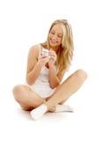 De zitting van de tiener op de vloer met een witte telefoon stock fotografie