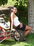 De zitting van de tiener op een rode ATV stock afbeelding