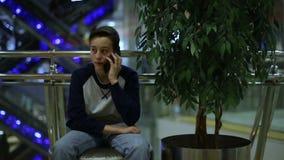 De zitting van de tienerjongen in winkel en het spreken smartphone stock videobeelden