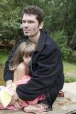 De zitting van de vader en van de dochter op de bank van rivier Stock Fotografie