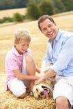 De Zitting van de vader en van de Zoon met binnen Hond op de Balen van het Stro Royalty-vrije Stock Afbeeldingen