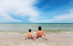 De zitting van de vader en van de zoon op het zandige strand. Stock Afbeeldingen