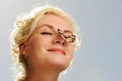 De zitting van de vlinder op een vrouwenneus Royalty-vrije Stock Afbeelding