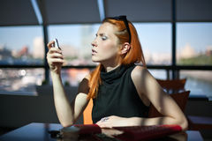 De zitting van de vrouw alleen in een koffie Stock Foto
