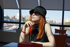 De zitting van de vrouw alleen in een koffie Royalty-vrije Stock Afbeeldingen