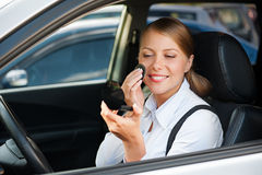 De zitting van de vrouw in auto en het van toepassing zijn maken omhoog Royalty-vrije Stock Afbeeldingen