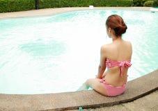 De zitting van de vrouw bij de rand van zwembad Stock Foto