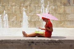 De zitting van de vrouw dichtbij fontein en het bekijken kaart royalty-vrije stock foto