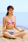 De zitting van de vrouw door het strand dat meditatie doet stock foto's