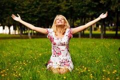De zitting van de vrouw in het gras en geniet van de zon Stock Foto's