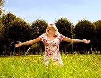 De zitting van de vrouw in het gras en geniet van de zon Royalty-vrije Stock Fotografie