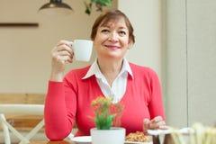 De zitting van de vrouw in koffie Stock Afbeeldingen