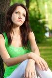 De zitting van de vrouw onder de boom en het dromen Stock Fotografie