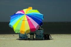 De zitting van de vrouw onder kleurrijke paraplu royalty-vrije stock foto